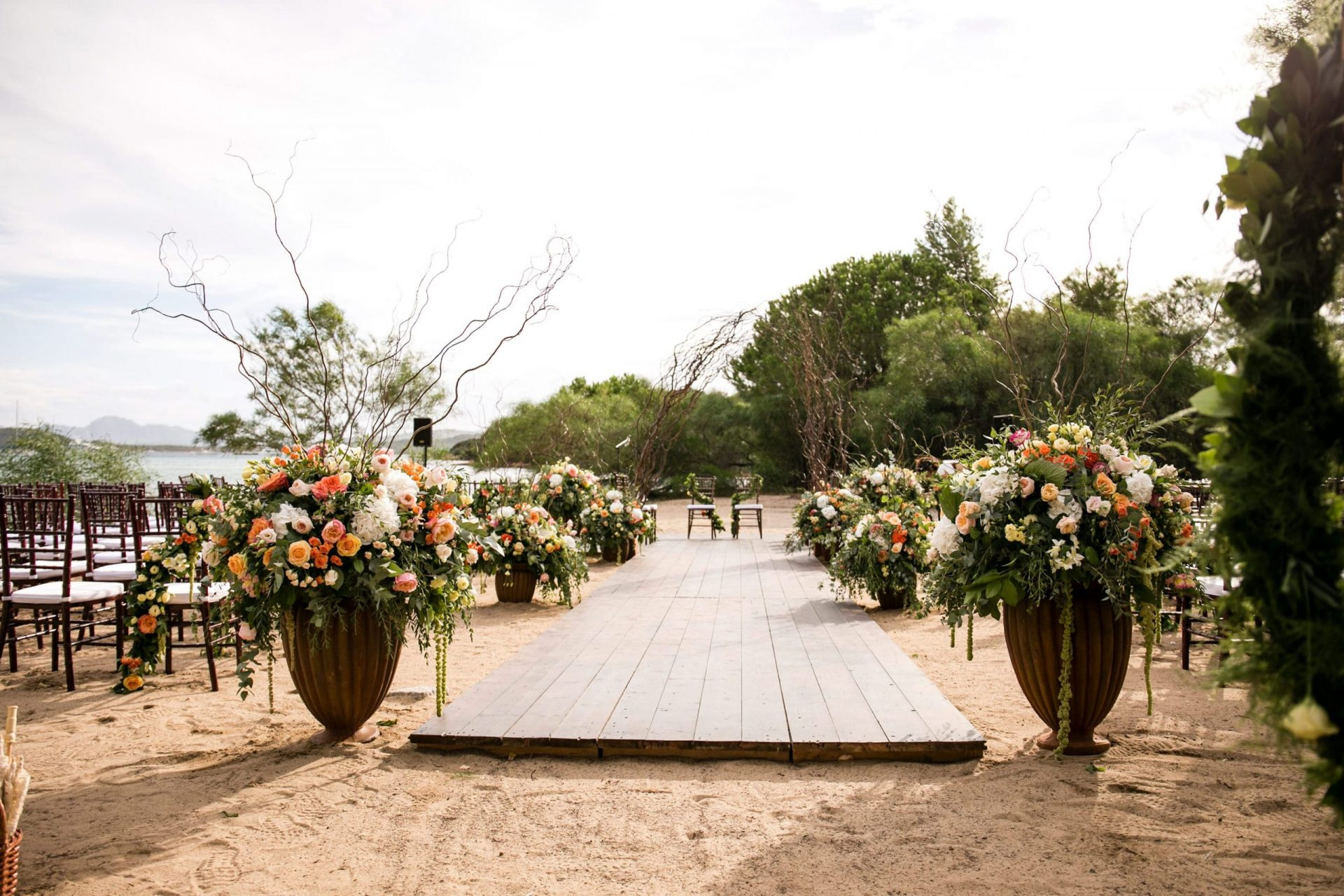 Lisa and Daniel, luxury wedding in Cala di Volpe, chic and colourful ceremony aisle on the beach