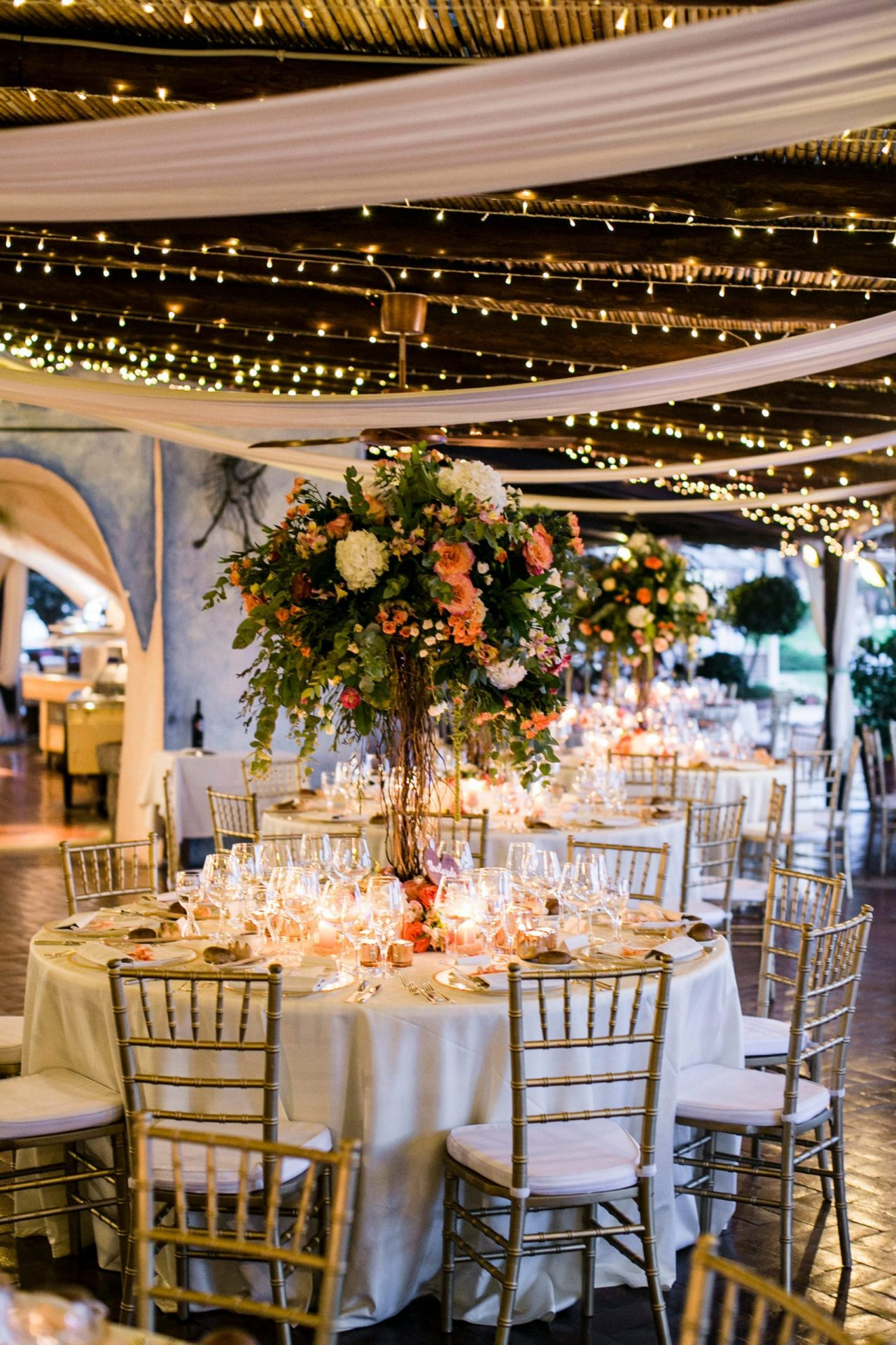Lisa and Daniel, luxury wedding in Cala di Volpe, green, orange and cream flower decoration